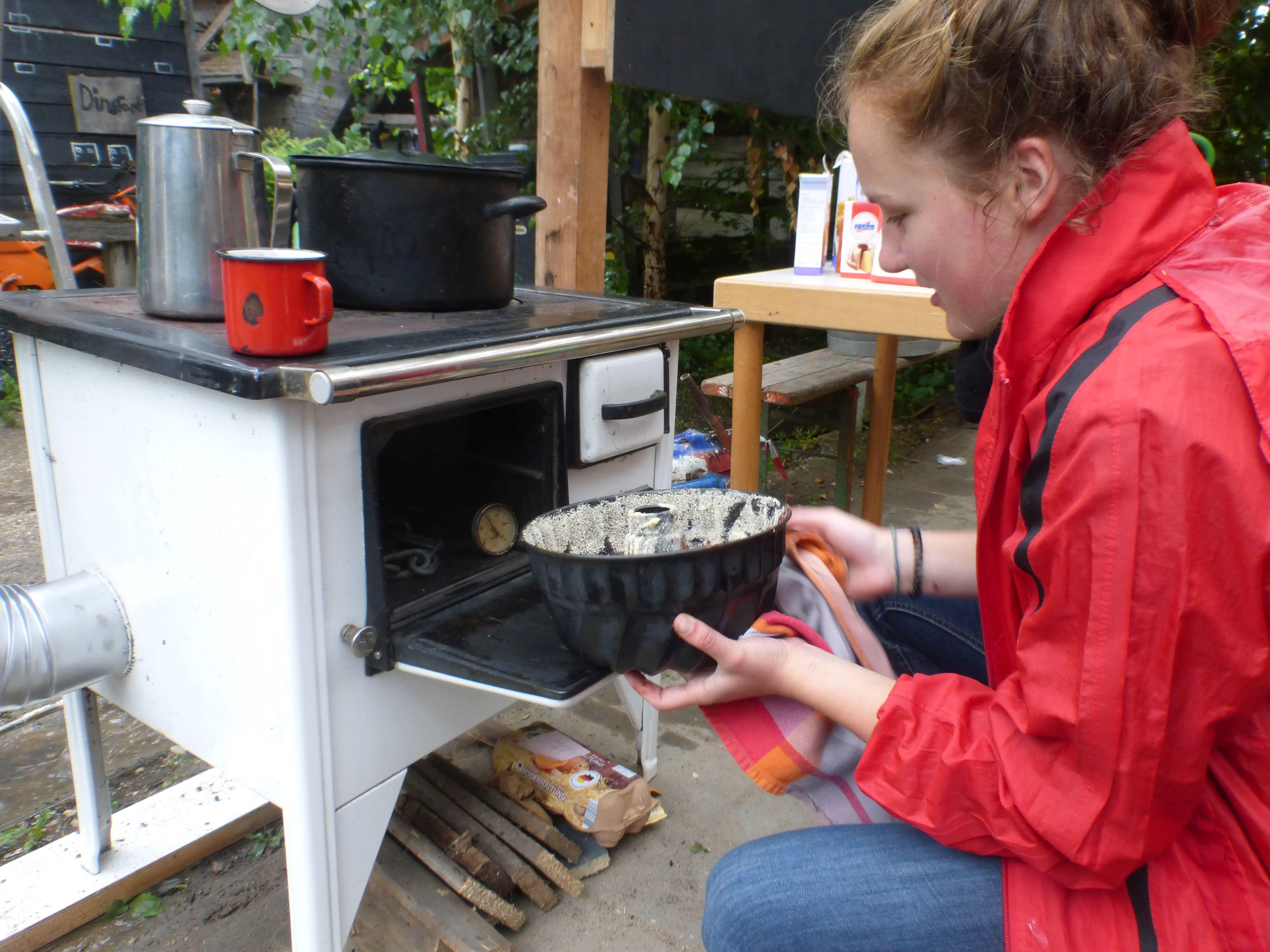 Mädchen stellt einen Kuchen in den Ofen