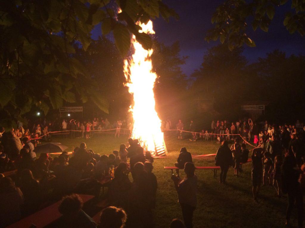 Menschen versammeln sich ums Sonnwendfeuer
