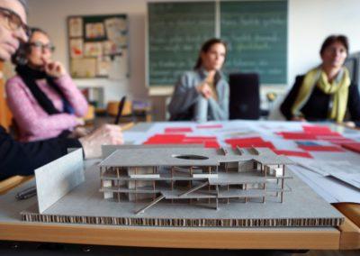 Im Vordergrund ein Pappmodell der ersten Architekturvorschläge, im Hintergrund sitzen Menschen an Tisch und blicken auf Modell..