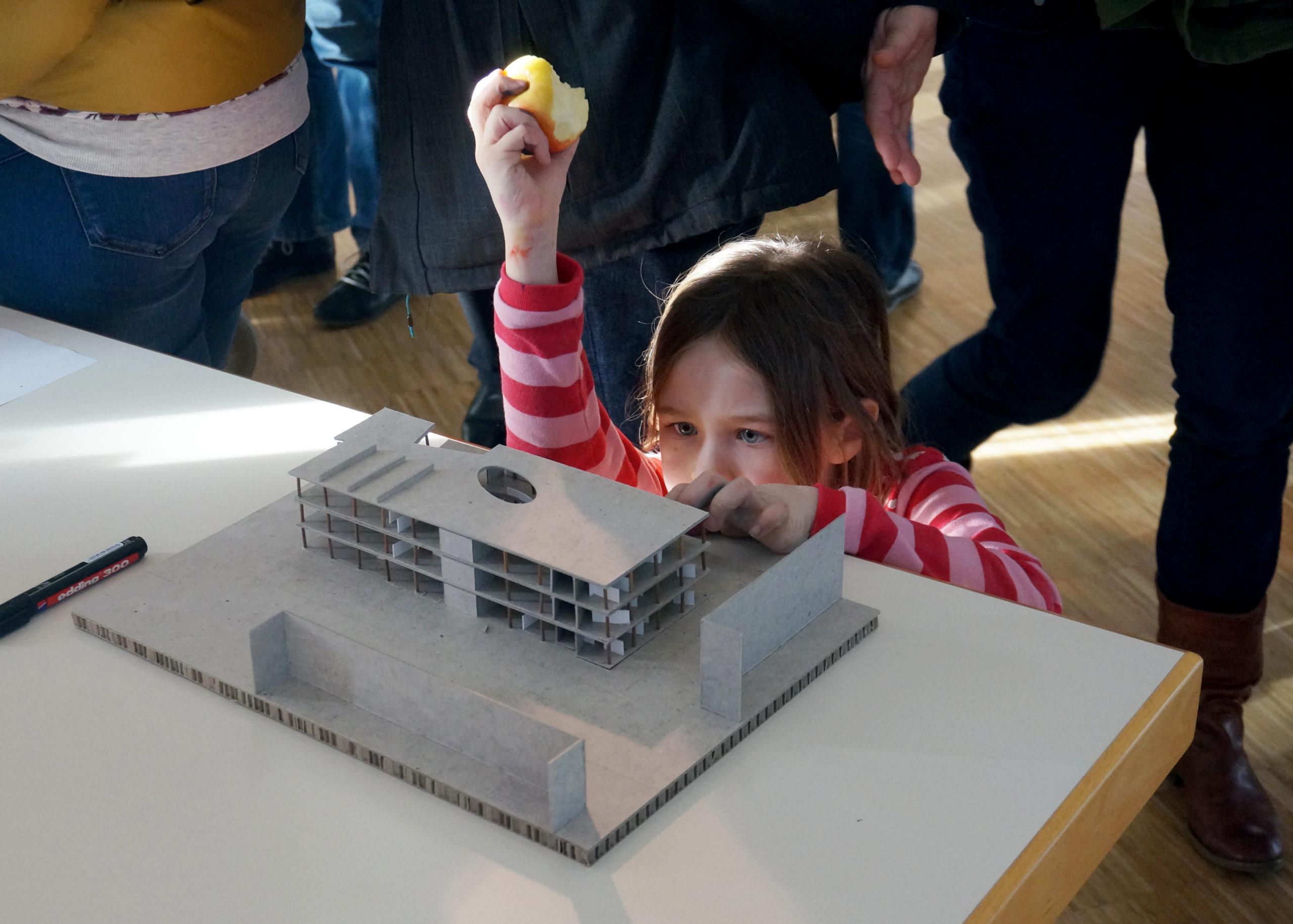 Junge Besucherin steht auf Augenhöhe mit Architekturmodell und betrachtet es. Dabei hält sie einen angebissenen Apfel in die Luft.